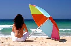 De zitting van de vrouw onder kleurrijke parasol op wit zandig strand Royalty-vrije Stock Foto