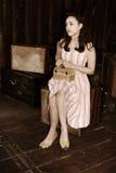 De zitting van de vrouw op bagage Royalty-vrije Stock Afbeelding