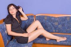 De zitting van de vrouw op bank Royalty-vrije Stock Fotografie