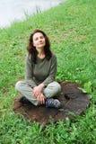 De zitting van de vrouw op de stomp. stock afbeelding