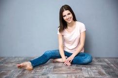De zitting van de vrouw op de vloer Stock Foto