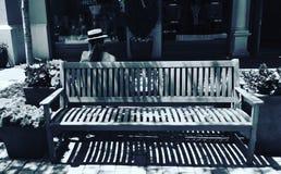 De zitting van de vrouw op een bank Stock Foto