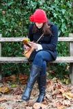 De Zitting van de vrouw op een Bank en Lezing een Boek Royalty-vrije Stock Afbeeldingen