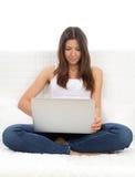 De zitting van de vrouw op een bank met moderne laptop verwerkt gegevens Stock Afbeelding