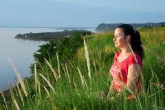 De zitting van de vrouw op een bank van een rivier royalty-vrije stock foto