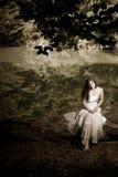 De zitting van de vrouw op een desaturated logboek, royalty-vrije stock fotografie
