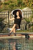 De zitting van de vrouw op een duikplank Stock Afbeeldingen