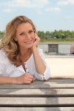 De zitting van de vrouw op een houten bank Stock Foto's
