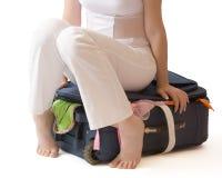 De zitting van de vrouw op een koffer die over wit wordt geïsoleerdu Royalty-vrije Stock Afbeelding
