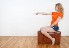 De zitting van de vrouw op een koffer en het richten van richting royalty-vrije stock foto's