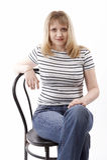 De zitting van de vrouw op een stoel Stock Afbeeldingen