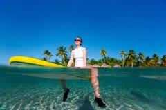 De zitting van de vrouw op een surfplank bij oceaan Royalty-vrije Stock Afbeeldingen