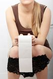 De zitting van de vrouw op een toilet stock foto