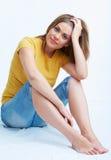 De zitting van de vrouw op een vloer Stock Foto's