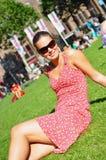 De zitting van de vrouw op gras in park stock afbeeldingen