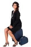 De zitting van de vrouw op haar koffer Royalty-vrije Stock Afbeelding