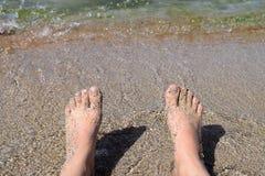 De zitting van de vrouw op het strand Royalty-vrije Stock Foto's