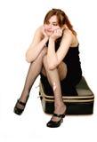 De zitting van de vrouw op koffer Stock Fotografie