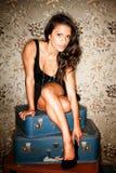De zitting van de vrouw op koffers die haar schoen aanpassen royalty-vrije stock foto