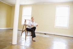 De zitting van de vrouw op ladder in lege ruimte stock fotografie