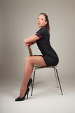 De zitting van de vrouw op moderne stoel Stock Foto