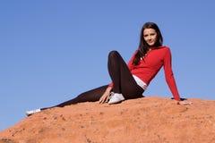 De zitting van de vrouw op rode rotsen Royalty-vrije Stock Fotografie