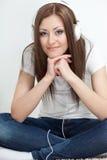 De zitting van de vrouw op tapijt en luistert aan de muziek Royalty-vrije Stock Afbeelding