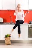 De zitting van de vrouw op teller in keuken stock foto's