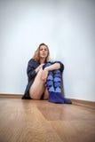 De zitting van de vrouw op vloer Stock Afbeeldingen