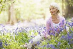 De zitting van de vrouw in openlucht met bloemen het glimlachen Royalty-vrije Stock Foto's