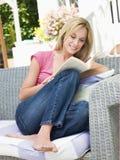 De zitting van de vrouw in openlucht op terras met boek het glimlachen Royalty-vrije Stock Fotografie