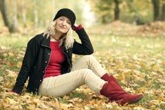 De zitting van de vrouw ter plaatse in park stock foto
