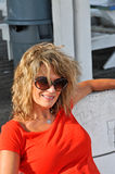 De Zitting van de Vrouw van de middenLeeftijd op een Witte Bank Royalty-vrije Stock Foto