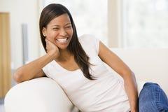 De zitting van de vrouw in woonkamer Stock Foto's