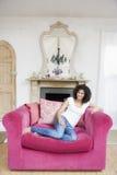 De zitting van de vrouw in woonkamer het glimlachen royalty-vrije stock fotografie