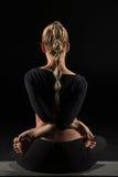 De zitting van de vrouw in yogapositie Stock Foto's