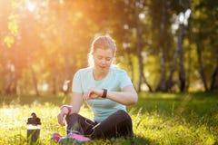 De zitting van de vrouwenagent op het gras die een slim horloge met behulp van stock afbeelding