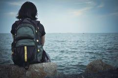 De zitting van de vrouwenreiziger op rots voor het rusten Stock Foto's