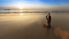 De zitting van de yogavrouw in lotusbloem stelt op het strand tijdens verbazende zonsondergang Stock Foto
