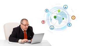 De zitting van de zakenman bij bureau en het kijken laptop met bol en zo Royalty-vrije Stock Afbeelding