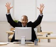 De zitting van de zakenman bij bureau het toejuichen Stock Fotografie