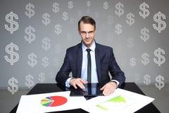 De zitting van de zakenman bij de lijst Op de lijststapels omslagen met documenten dollartekens op achtergrond Stock Foto's