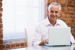 De zitting van de zakenman in bureau bij laptop het glimlachen Royalty-vrije Stock Foto's