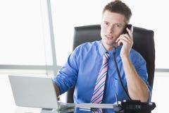 De zitting van de zakenman in bureau met laptop Stock Foto's