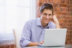 De zitting van de zakenman in bureau met laptop het glimlachen Royalty-vrije Stock Afbeeldingen