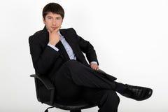 De zitting van de zakenman in een leunstoel Royalty-vrije Stock Fotografie