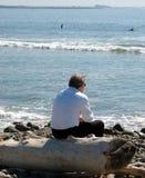 De zitting van de zakenman op een logboek bij het strand royalty-vrije stock afbeelding