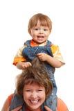De zitting van de zoon op moederschouders Stock Foto