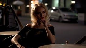 De zitting van de Fatalevrouw bij lijst in restaurant en seductively het kijken, sexy dame stock fotografie