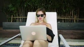De zitting van de Freelancervrouw op een lanterfanter dichtbij de pool en het werken aan laptop, langzame motie stock video